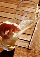 Germany, Bavaria, Human hand pouring wheat beer in glass, close up