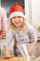 Germany, Mother and daughter preparing cookies, smiling