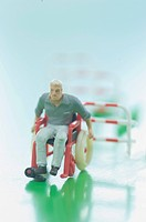 Figurine in wheelchair, hurdle in background