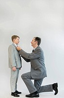 Father adjusting sons tie, smiling