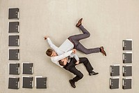 Businessmen fighting in office between files