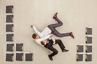 Businessmen fighting in office between files