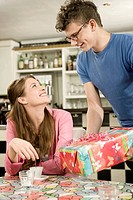 Germany, Bavaria, Munich, Young man surprising with gift to woman in cafe, smiling