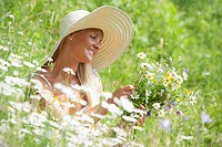 Austria, Altenmarkt-Zauchensee, Mid adult woman with flowers in meadow, smiling
