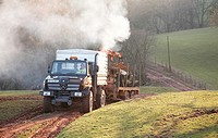 Farmer with a Mercedes Unimog, with a flatbed moving trees that were toppled in a storm
