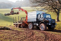 Farmer in South Wales, UK, with a Mercedes Unimog, loading up a flatbed with trees that were toppled in a storm using a mechanical grabber