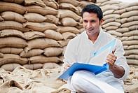 Man sitting on wheat sack holding a file, Anaj Mandi, Sohna, Gurgaon, Haryana, India