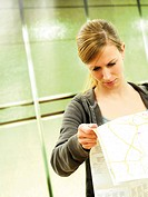 Young woman with city map, metro station