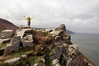 Jubilant Female Walker On Top Of Rocks Along The South West Coast Path Near Lynmouth, Exmoor, United Kingdom