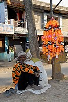 Man In An Orange Lowered Shirt Sells Orange Plastic Puja Flowers, Karnataka, India