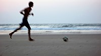 Person Playing Football On Mandrem Beach In Goa, India