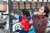 Kathmandu, Nepal. Mother and Child Spinning Prayer Wheels at Swayambhunath Temple