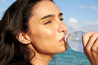 Hispanic woman drinking water bottle on beach