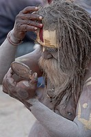 Pashupatinath, Nepal. Sadhu (Holy Man) at Nepal's Holiest Hindu Temple. He checks himself in a mirror as he begins to paint his face