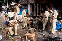 Policemen inspecting remains of taxi damaged by powerful explosives at Zaveri Bazaar in busy Kalbadevi area , Bombay Mumbai , Maharashtra , India Augu...