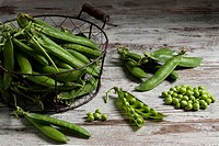 Pea Pods and Shelled Peas on Wooden Table.
