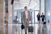 Smiling businessman carrying briefcase and pulling suitcase in airport