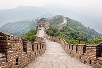 Beijing, China-August 17, 2010: Thousands of tourists visit daily the Chinese wall. A family walking on the Great Wall of China that the horizon is lo...