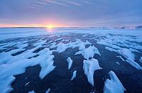 Sun setting over a frozen lake in Ontario, Canada.