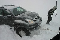 Car stranded in deep snow during snowstorm, Iceland.