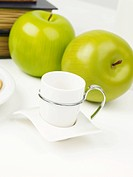 tea cup and apples on table