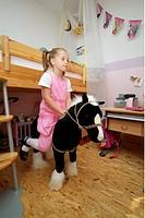 Schulanfang - der erste Schultag - Maedchen auf Spielpferd nach den ersten Hausau. - Gro¯hansdorf, Schleswig-Holstein, 24/08/2006