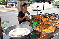 Street vendor using a wok to fry food in Bangkok, Thailand.