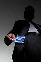 GERMANY, HAMBURG, 24.03.2010, Man in a suit with empty pockets in the national colours of Greece. Symbol: national bankruptcy of Greece. - Hamburg, Ge...