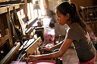A young girl works in a village textile factory outside of Phnom Penh, Cambodia.