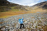 Female hiker hikes over rocky terrain in Tjäktjavagge on Kungsleden trail, Lappland, Sweden.