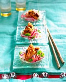 Glass noodle salad with black pepper chicken served on three glass dishes with chopsticks on a turquoise tablecloth