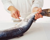 Holding the tail of a salmon and using a fork to scrape off scales