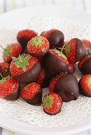 Strawberries half coated with chocolate, on a white plate, close up