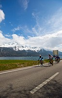 Cyclists riding bicycles on the road at lakeside, Como, Lombardy, Italy