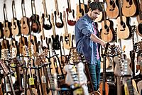 Man choosing acoustic guitar in guitar shop
