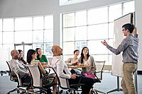 Businessman giving presentation to colleagues in conference room.