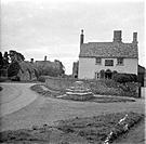 The Plough Inn, Kelmscott, Oxfordshire. The base of a medieval preaching cross stands on the verge in front of the Plough Inn in Kelmscott village. Th...