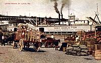 Levee scene, St Louis, Missouri, USA, 1910. Horse-drawn wagons on the levee on the bank of the Mississippi beside oiiles of cargo. A river boat is on ...