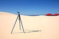 digitally manipulated image of a tripod in a sand dune -looking towards red dress shapes that are like an island on the horizon.