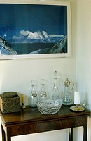 Picture above mahogany console table ith collection of antique glass decanters
