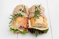 Baguette sandwiches with rosmary on white wood boards
