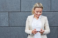 Germany, Businesswoman holding smart phone