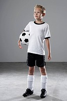 Boy in soccer jersey holding ball