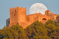 Full moon rising at sunset over 14th century Puig de Maria sanctuary. Pollensa area. Majorca, Balearic islands, Spain