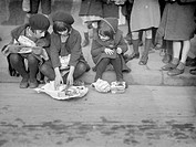 Poor working class children in London's East End, queueing up for the 'Fern Street Settlement': : Delighted little girls, playing with their bundles o...