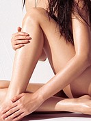 Sensual artistic closeup of a young woman bare legs and hands with shiny skin and wet hair.