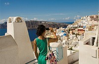 Greece Santorini Oia Cyclades white buildings and steep mountains Greek Islands beautiful peaceful place Greek with Phillipino Asian woman tourist tak...