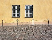 Chain railing, building facade and pedestrian walkway with windows. Cobbled street in old town in Tallinn, Estonia.
