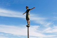 Man standing and balancing on a metal post, looking towards expansive sky, on Surprise Mountain, Alpine Lakes Wilderness, Mt. Baker-Snoqualmie Nationa...