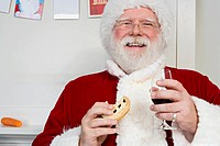 Father christmas eating a mince pie with a glass of sherry
